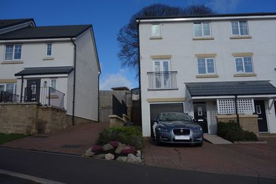 Front elevation with parking for three cars and side accessto back garden.