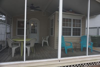 Screened front porch with dining & lounge chairs