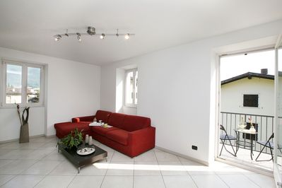 The spacious and bright living room with acces to the balcony