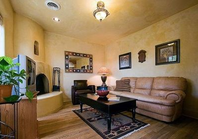 The living room has natural wood floors and a kiva fireplace.