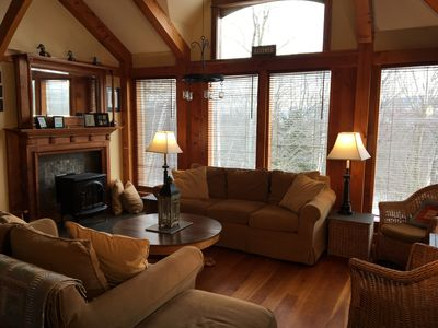 Sunroom view showing gas fireplace and antique mantel.  Sunny and comfortable.
