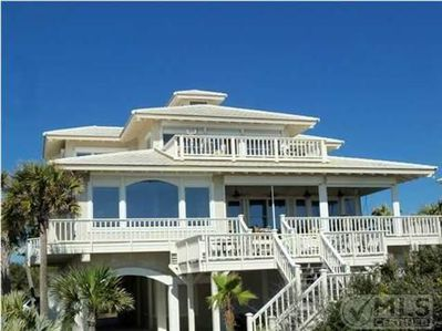 View of home from the beach with stairway to main deck and surrounding palms