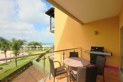The balcony with a 4-seat table, a BBQ-grill, and your stunning ocean views!