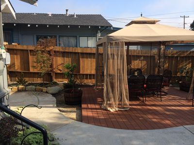 Backyard with dining area under canopy on raised trex decking