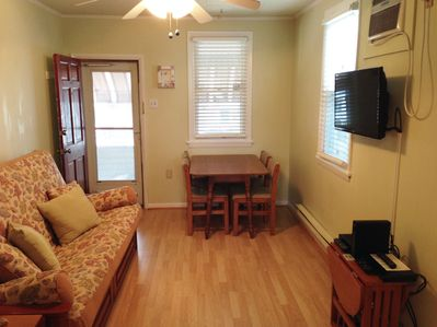 Living Room with queen futon with under storage. Dining Table and 4 chairs, TV.