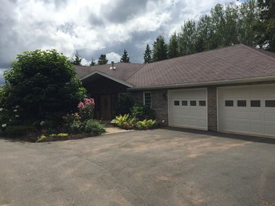 Front entry of summer home with gardens, parking and double car garage