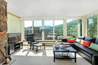 Sunny living room with mountain views feature a flat screen TV and floor to ceiling windows.
