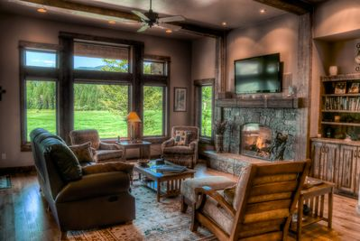 Great room with rock fireplace, comfortable seating, spectacular views and HDTV.
