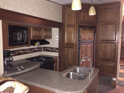 Kitchen area with double sink, cook top, oven and refrigerator & microwave