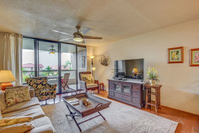 Light, bright living room with large screen TV and ceiling fan.