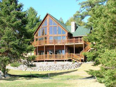 Two large decks and a gently sloping yard to a flat sandy beach.