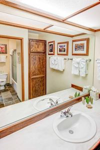 White bathroom with wood cabinets