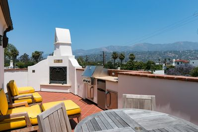Balcony - Second-floor balcony with kitchenette, gas fireplace, dining table, seating, and views of the Santa Ynez Mountains.