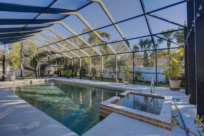 Beautiful screened-in pool with spa, barbecue and lots of seating.
