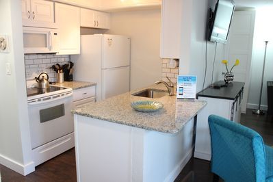 Well-stocked Kitchen with a pass-through that ensure no one misses out on the fun with granite counter tops & breakfast bar, stainless steel sink & subway tile backsplash.