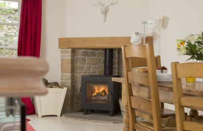 Ground floor:  Enjoy cosy suppers next to the wood burning stove. French doors to outside eating area