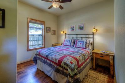 queen bedroom with cozy quilts, ceiling fans, and Tiffany lighting