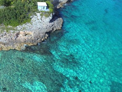 Aerial of the cottage way out on the point. Two other cottages off screen.