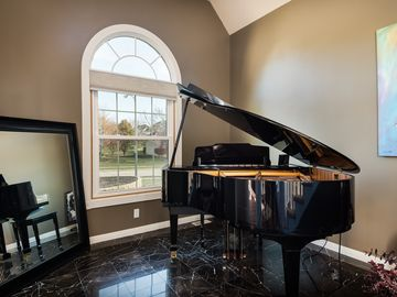 Music room with beautiful player grand piano.