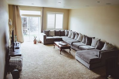 """The family room has a spacious couch that easily seats 12, and a 70"""" 4K TV"""