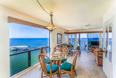 Round dining table with 4 rattan chairs facing large window with oceanfront view