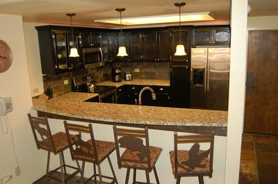 Kitchen features slab granite, stainless appliances and seating for 4 at bar