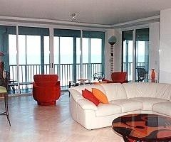 living room with marble floors, view of beach