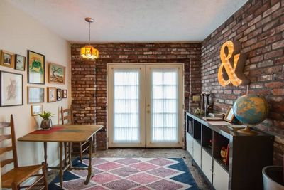 Bright entry area and dining nook with exposed brick wall.