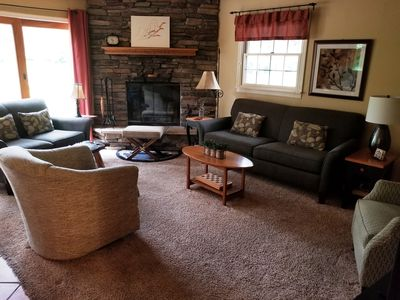 Living Room with Wood Burning Stone Fireplace and walk out deck