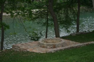 There's a fire pit and stone patio near the river