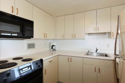White kitchen with fridge, sink, coffee maker, and black stove and microwave