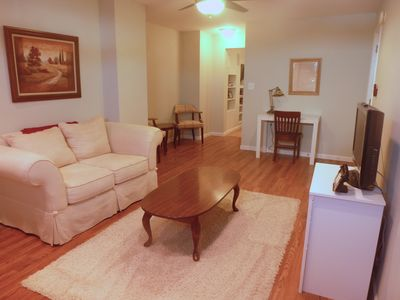 Spacious living area with TV, desk, and multiple sitting areas