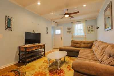 The living room features a comfy sofa, cable TV and hardwood floors with rugs.