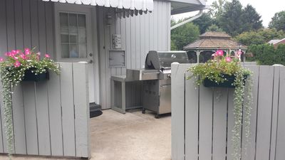 Large Weber Summit natural gas grill with side burner just outside kitchen door