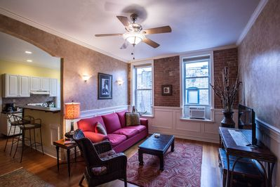 Living room has exposed brick . Television is a smart tv, includes cable.