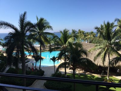 Afternoon view of pool, palm trees and the ocean from the balcony.