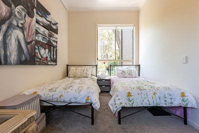Inside of the guest room with two single beds