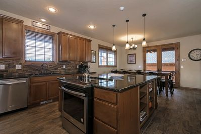 Large luxurious kitchen with granite countertops and stainless appliances.