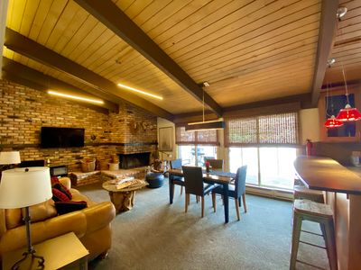 Living room & dining area. Large HDTV, wood fireplace, riverfront deck with BBQ