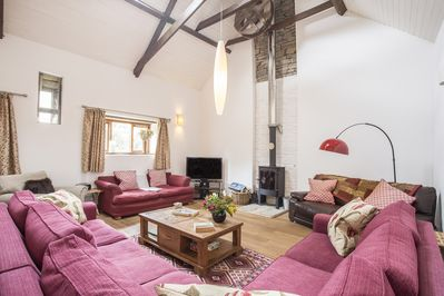 Double height lounge with huge comfy sofas and woodburner