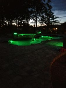 night time view of pool and tanning ledge