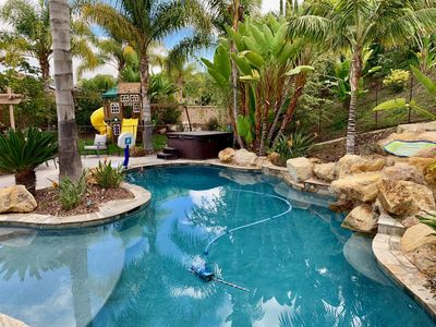 Backyard with pool, spa, BBQ, playset, firepit, large outdoor table & trampoline