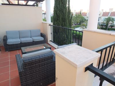 Chairs, sofa and Table with umbrella on the balcony