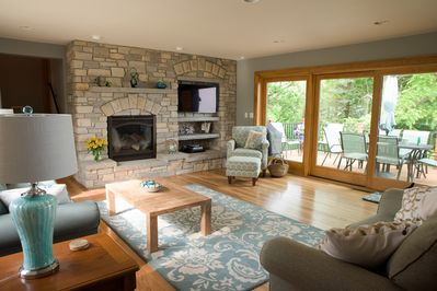 Living area: floor to ceiling windows w exit to back yard porch, fireplace, TV