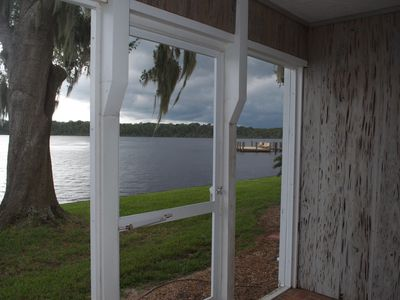 Photo for Land of a million sunsets! Riverfront condo, boat dock, pool, patio, grills.