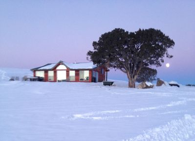 As the moon sets, the sun rises over the Ranch and is reflected in the windows.