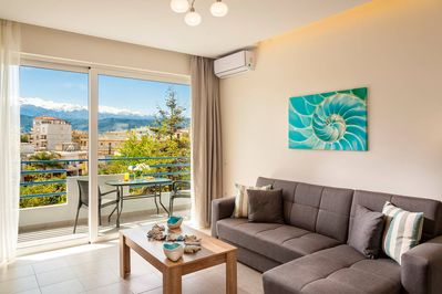 Big sunny living room with big corner sofa,breathtaking view to city&mountains