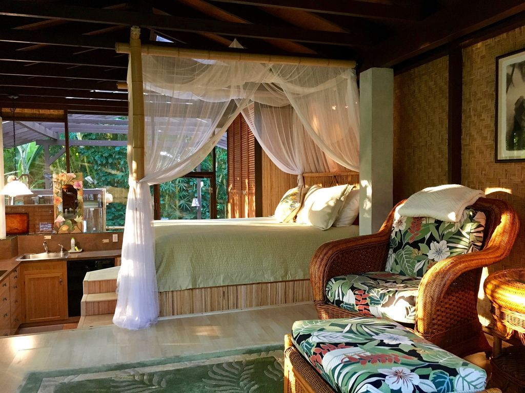 Cottage Interior: Dreamy queen bed and rattan lounging chair.