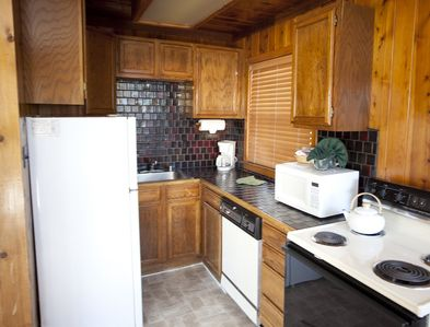 A well equipped kitchen with stove and dishwasher.