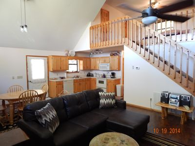 Interior of chalet with stairs to the master loft. Oak cabinets in open kitchen.